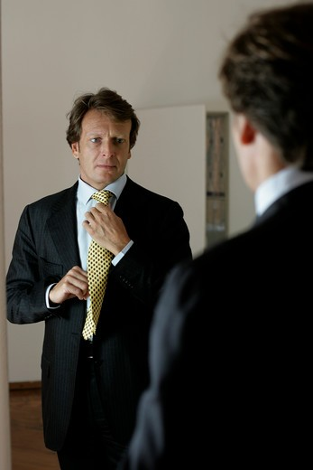 Stock Photo: 4292-74631 Portrait of a man doing up his tie in front of a mirror
