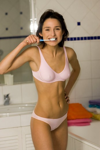 Portrait of a woman brushing teeth : Stock Photo