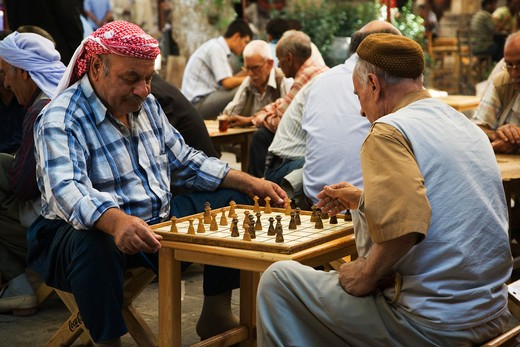 Turkey, Urfa, Bazaar, in the open court of a tea house, men play a variant of chess : Stock Photo