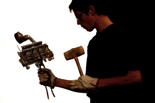 Manual worker in fabric working holding a piece of industrial fan : Stock Photo