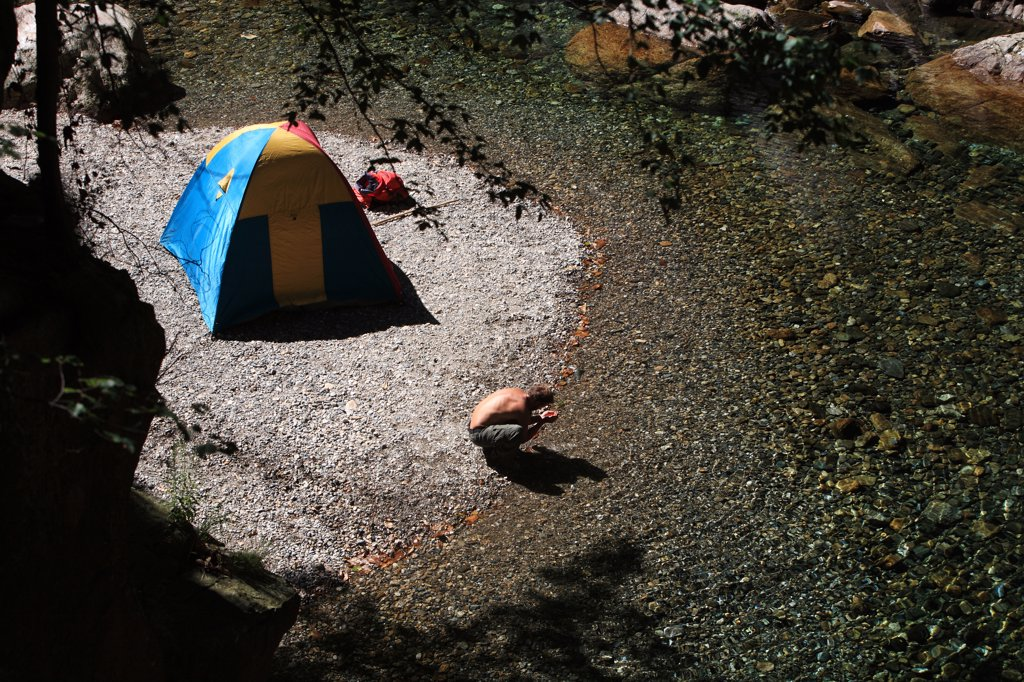 Man camping on river bank : Stock Photo