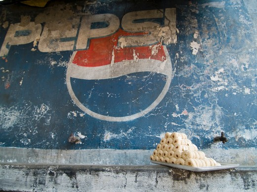 Local sweets contrast with a global soft drink brand in Orcha, Madhya Pradesh, India : Stock Photo
