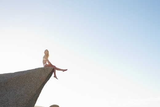 Young woman sitting on rock under blue sky : Stock Photo
