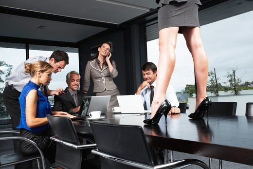 Stock Photo: 4294R-1247 Business meeting with woman standing on conference table