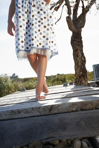 Girl walking on wooden path : Stock Photo