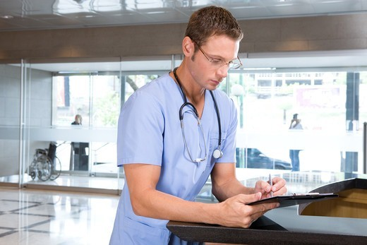 Stock Photo: 4294R-1445 Young doctor writing on clipboard