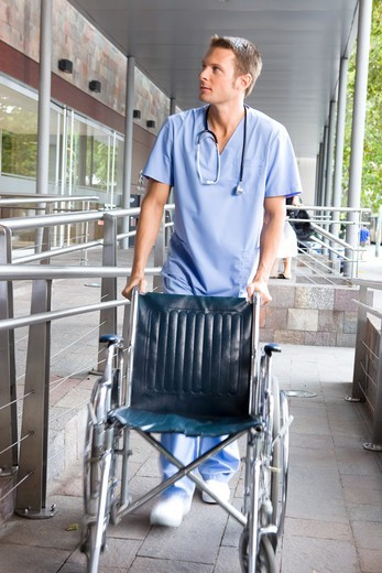 Stock Photo: 4294R-1449 Male nurse pushing wheelchair