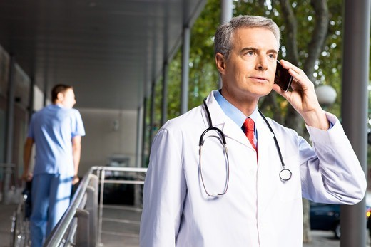 Stock Photo: 4294R-1453 Doctor on the phone outside hospital