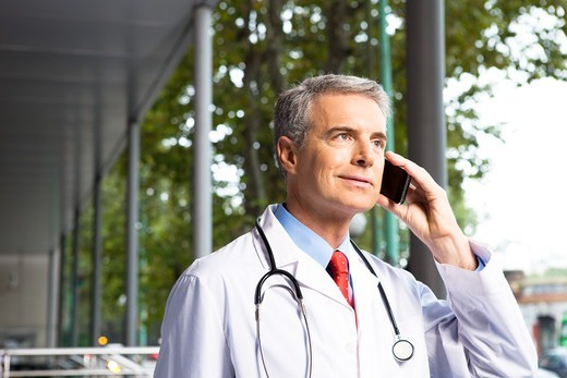 Stock Photo: 4294R-1454 Doctor on the phone outside hospital