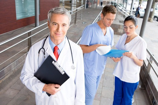 Smiling doctor and healthcare workers : Stock Photo
