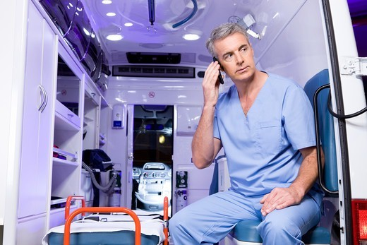 Stock Photo: 4294R-1488 Paramedic sitting in ambulance car