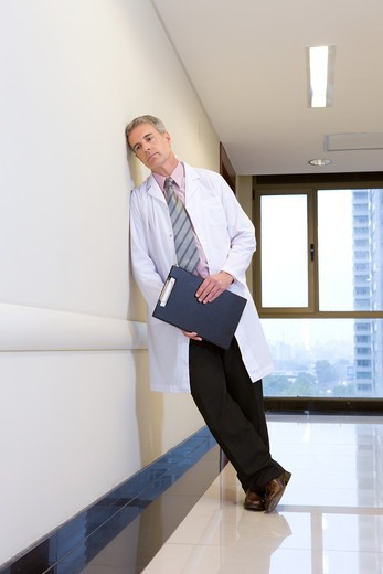 Stock Photo: 4294R-1506 Doctor leaning against wall on hospital corridor