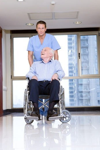 Stock Photo: 4294R-1510 Male nurse pushing senior in a wheelchair