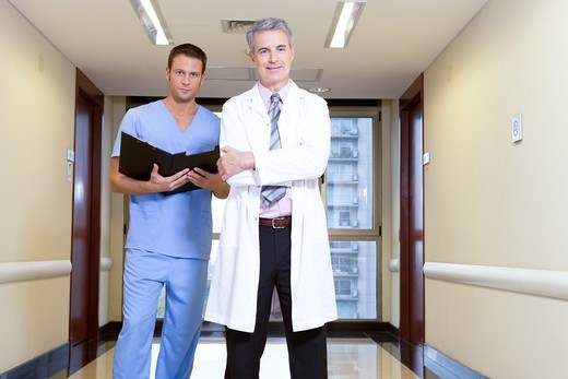 Stock Photo: 4294R-1512 Doctor and male nurse on hospital corridor