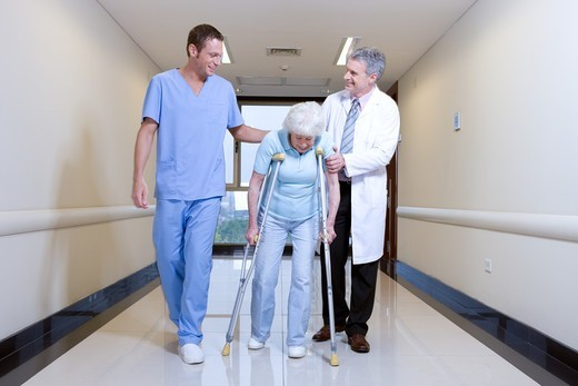Two doctors supporting old lady : Stock Photo