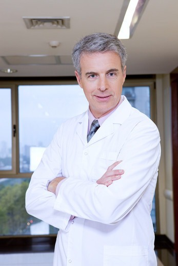 Doctor in hospital with arms crossed : Stock Photo