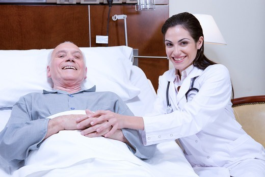 Doctor and senior man in hospital bed : Stock Photo