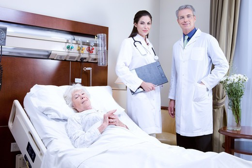 Stock Photo: 4294R-1541 Doctors and senior woman in hospital bed