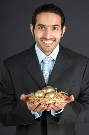 Stock Photo: 4303R-1415 Businessman holding nest with golden egg, smiling, portrait