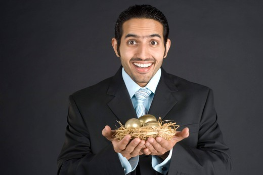 Businessman holding nest with golden egg, portrait : Stock Photo