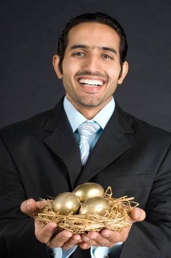 Stock Photo: 4303R-1418 Businessman holding nest with golden egg, smiling, portrait