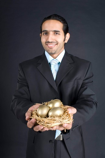 Businessman holding nest with golden egg, smiling, portrait : Stock Photo