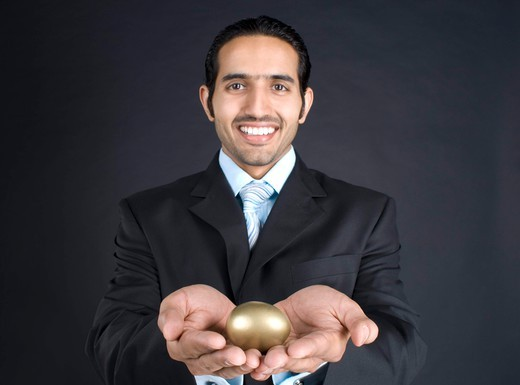 Businessman holding golden egg, smiling, portrait : Stock Photo
