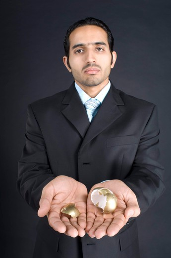 Stock Photo: 4303R-1430 Businessman holding broken golden egg in cupped hands