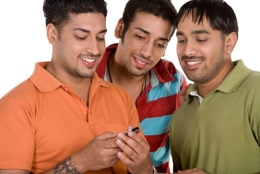 Friends reading text message, smiling : Stock Photo
