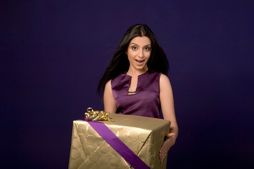Stock Photo: 4303R-1729 Young woman holding gift, portrait