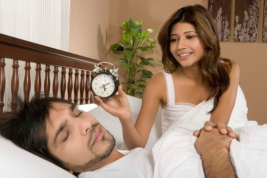 Stock Photo: 4303R-1792 Wife waking up husband with clock
