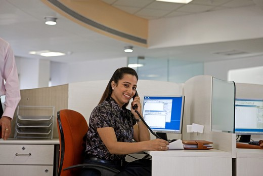 Stock Photo: 4303R-2352 Businesswoman talking on telephone at the office, smiling