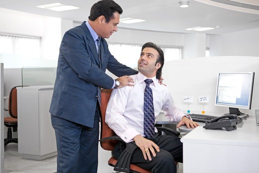 Two businessmen talking in the office, smiling : Stock Photo