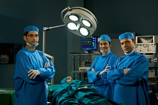Stock Photo: 4303R-2509 Three confident surgeons in the operating room
