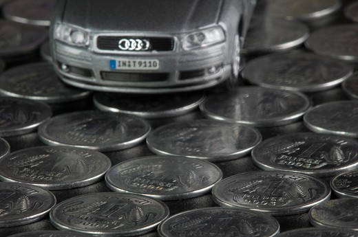Stock Photo: 4303R-2750 Toy car on top of indian rupee coins