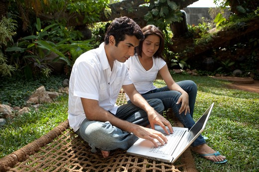 Stock Photo: 4303R-3215 Couple with laptop sitting in the garden