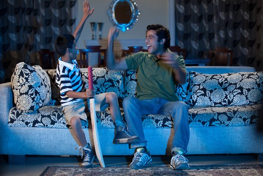 Father and son watching sports program in the television, cheering : Stock Photo
