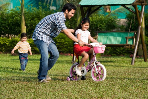 Stock Photo: 4303R-3405 Daughter learning bicycle with her father, son chasing