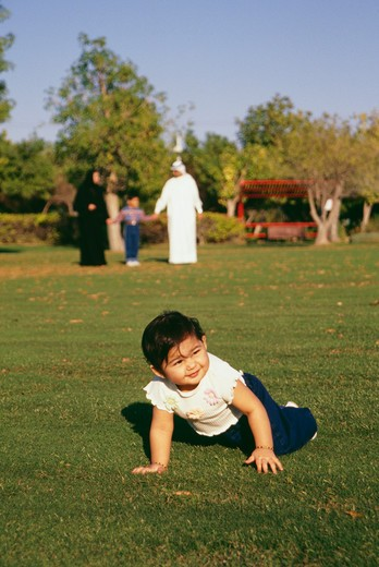 A baby smiles while crawling on the ground. : Stock Photo
