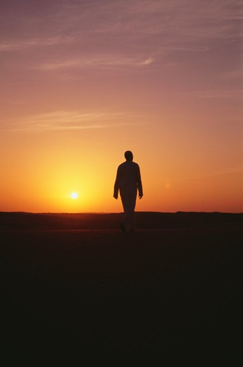 A man seen walking at sunset. : Stock Photo