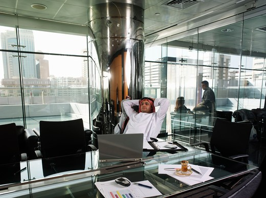 Businessman relaxing in a conference room : Stock Photo