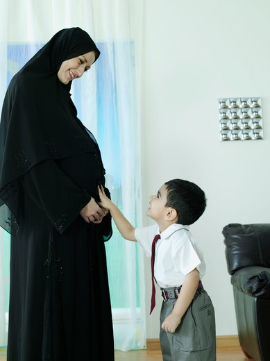 Stock Photo: 4304R-2092 Child touch the tummy of his pregnant mother.