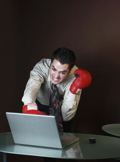 Young Businessman with boxing gloves attacking computer : Stock Photo