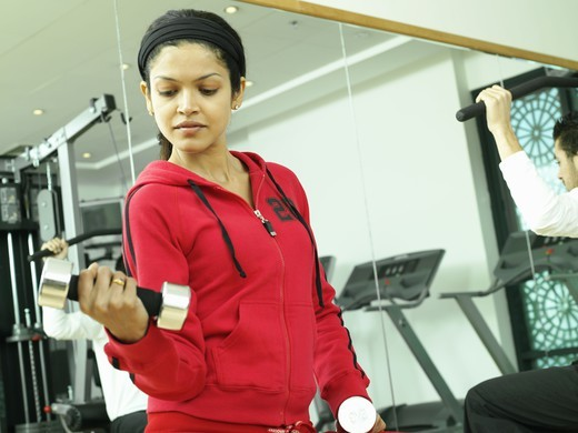 Stock Photo: 4304R-2495 Young lady lifting weights.