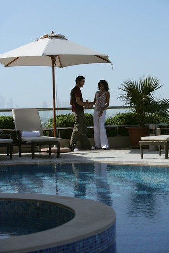 Stock Photo: 4304R-2529 Young couple relaxing beside the pool.