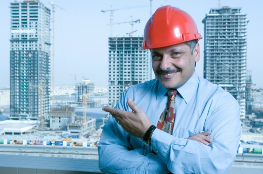 Stock Photo: 4304R-4515 Portrait of a Engineer with the building constructions in the background in Dubai