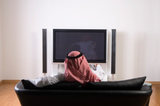 Stock Photo: 4304R-4591 Young Arab man watching TV