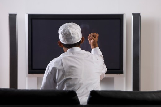 Young Arab man watching TV : Stock Photo
