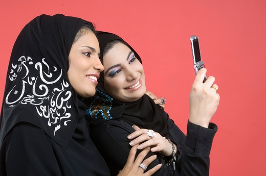 Stock Photo: 4304R-4682 Two Arab Ladies standing cheek to cheek with cell phone
