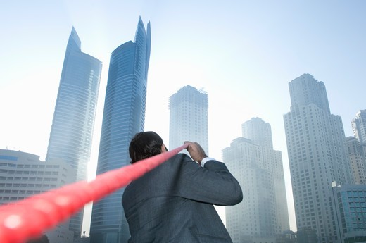 Stock Photo: 4304R-4800 Businessman tugging rope, Towers seen through the mist in the background